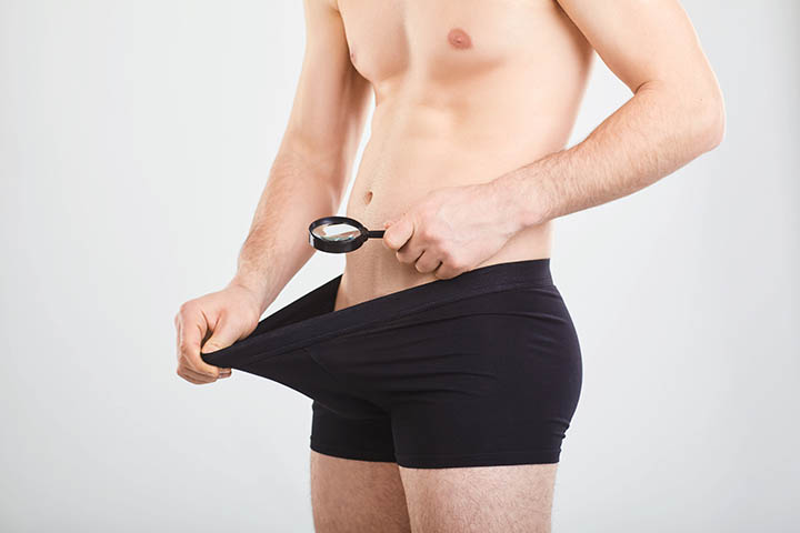 man checking out his penis with magnifying glass